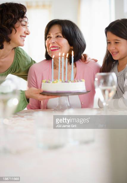 Mother and daughter giving birthday cake to grandmother