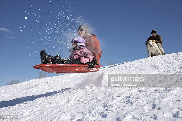 mother and daughter go off jump on a sled - 橇 ストックフォトと画像