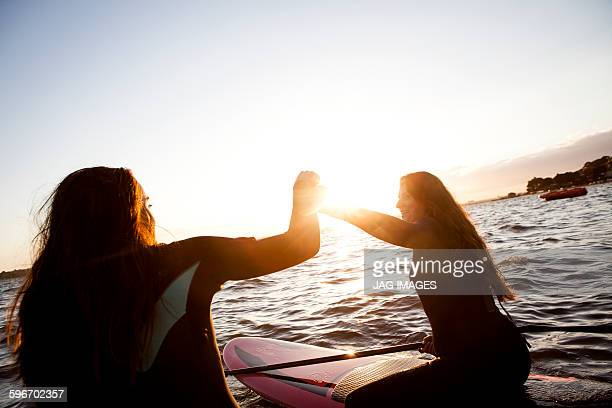 mother and daughter go paddle boarding