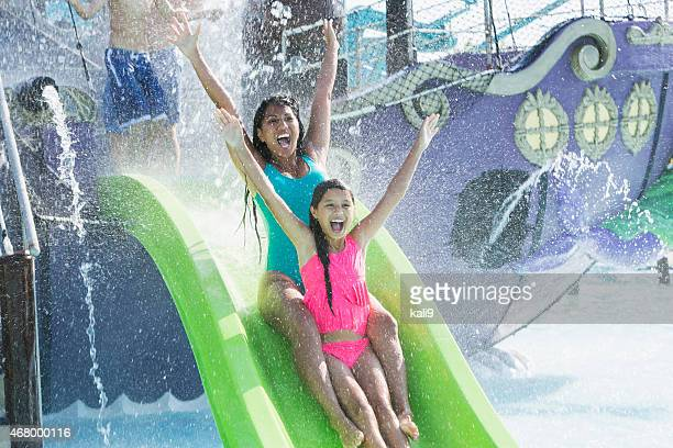 Mother and daughter going down water slide