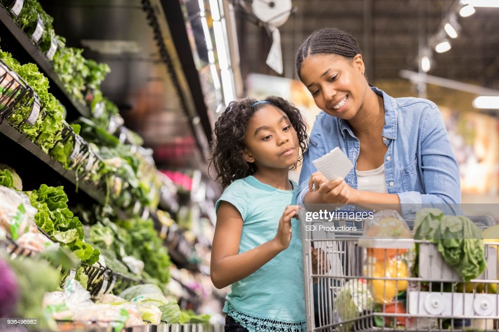 Mother and daughter grocery shop together using list : Stock Photo