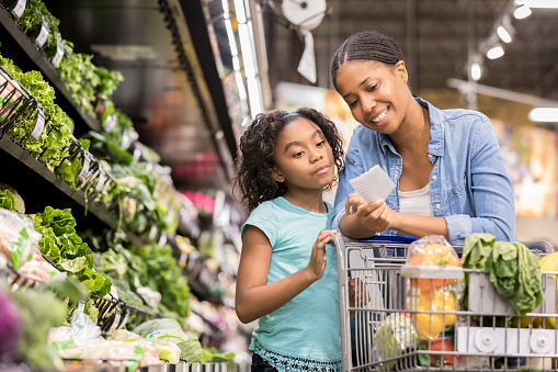Mother and daughter grocery shop together using list - gettyimageskorea
