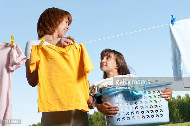 A mother and daughter handing laundry from a clothesline