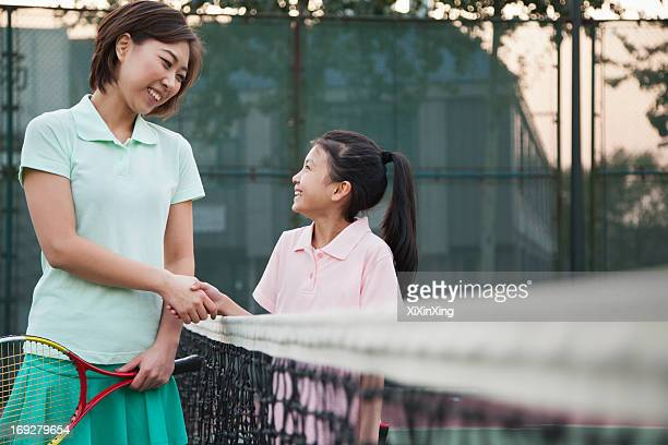 Mother and daughter handshaking over the tennis net