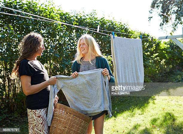 Mother and daughter hanging up laundry