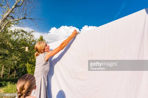 mother and daughter hanging white bed sheets to dry outside on the fresh air - bleach stock pictures, royalty-free photos & images