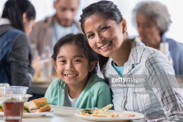 mother and daughter have lunch in soup kitchen - homeless shelter stock pictures, royalty-free photos & images