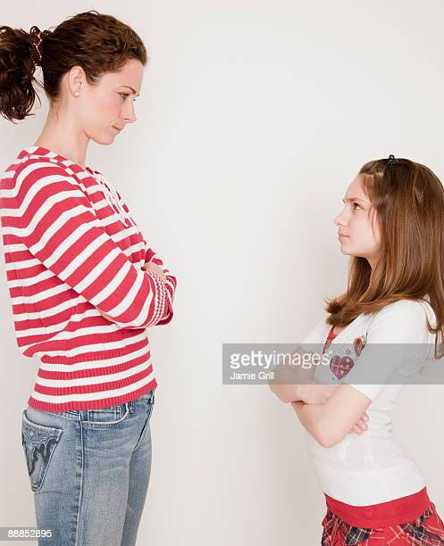 Mother and daughter (10-11 years) having argument, standing face to face
