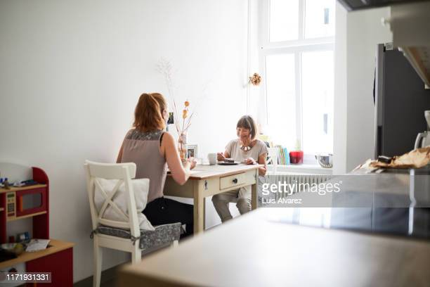 mother and daughter having breakfast in kitchen - nur erwachsene stock-fotos und bilder