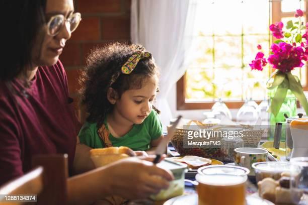 mother and daughter having breakfast - sentar se imagens e fotografias de stock