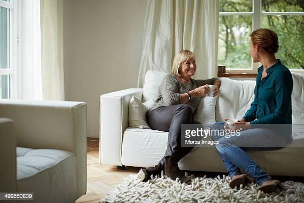 mother and daughter having coffee on sofa - só adultos imagens e fotografias de stock