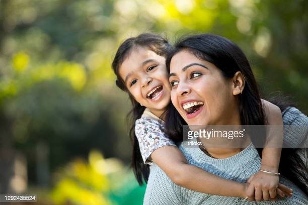 mother and daughter having fun at the park - indian ethnicity stock pictures, royalty-free photos & images