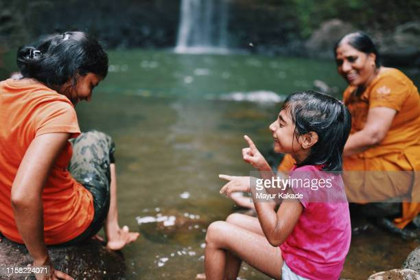 mother and daughter having fun at the waterfall - india stock pictures, royalty-free photos & images