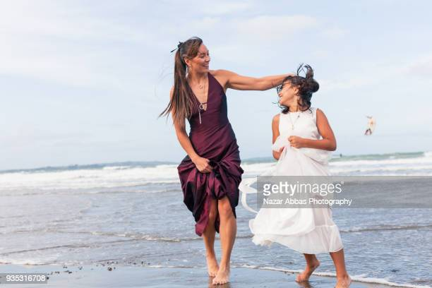 Mother and daughter having fun during a walk at beach.