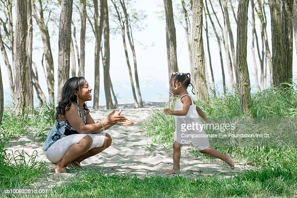 Mother and daughter (2-3) having fun in grove near seashore, side view