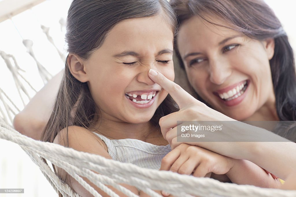 Mother and daughter having fun in hammock : Stock Photo