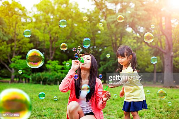 mother and daughter having fun in park with soap bubbles - japanese mom stock photos and pictures