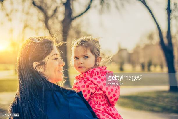 Mother and daughter having fun in the public park on a beautiful sunny day