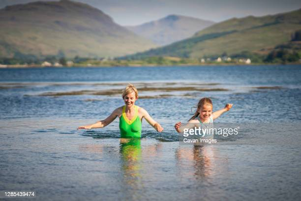 mother and daughter having fun in the sea - sea stock pictures, royalty-free photos & images