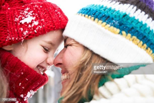 mother and daughter having fun in winter - kopfbedeckung stock-fotos und bilder