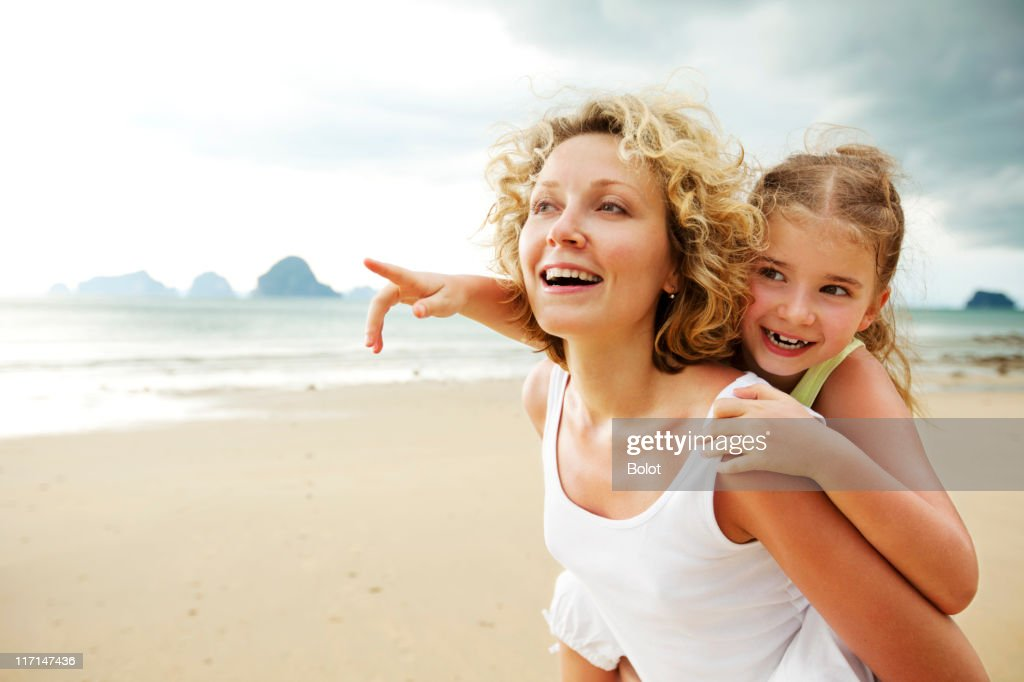 Mother and daughter having fun on beach : Stock Photo
