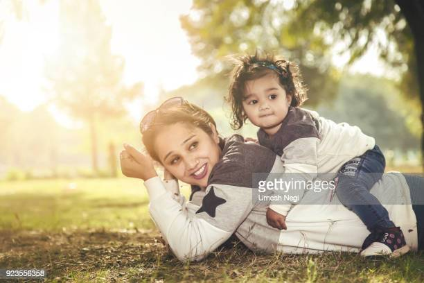 mother and daughter having fun on the grass in a park - asian baby stock photos and pictures