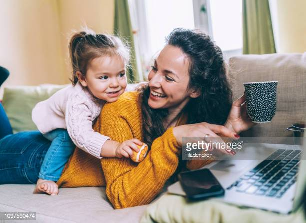mother and daughter having fun online - mom stock pictures, royalty-free photos & images