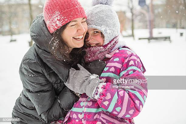 Mother and daughter having fun playing in fresh fallen snow.