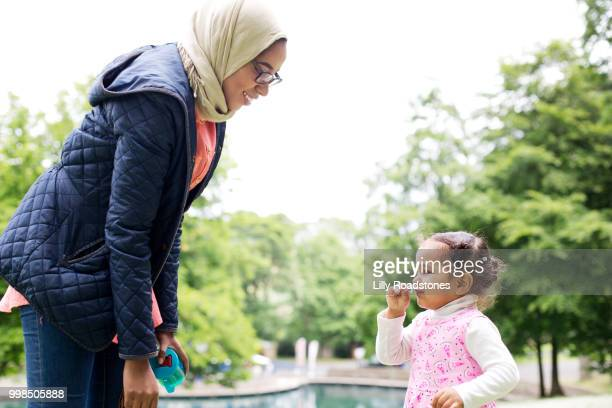 Mother and daughter having fun smelling flowers in public park