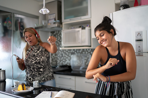 Mother and daughter having fun together while dancing in the kitchen 1132148244
