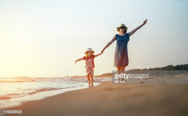 mother and daughter having fun with kids at vacation - water's edge stock pictures, royalty-free photos & images