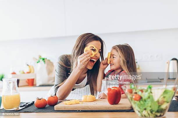mother and daughter having fun with the vegetables - gezonde voeding stockfoto's en -beelden