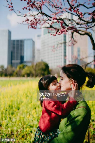 Mother and daughter having intimate moment under plum blossoms