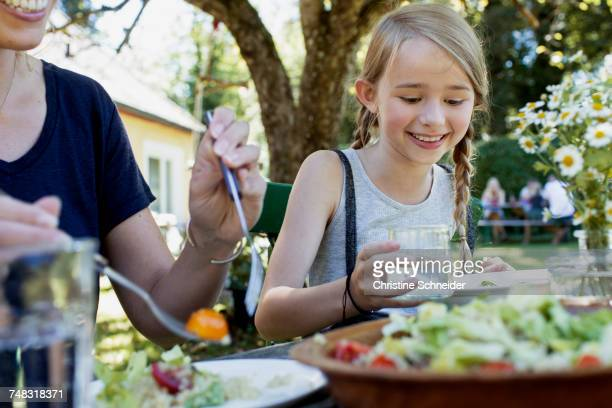 Mother and daughter having lunch in garden