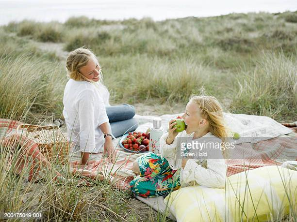 Mother and daughter (6-8) having picnic on beach, smiling