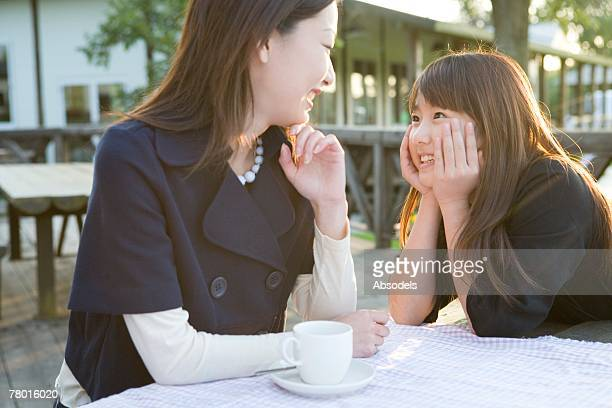 Mother and Daughter having tea outside, smiling