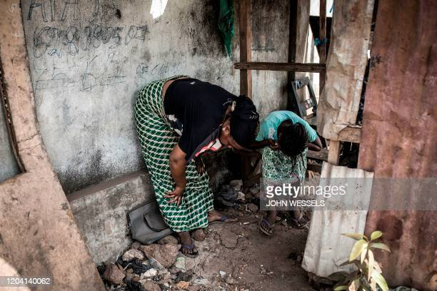 A mother and daughter hide away after being affected by tear gas along the axis of democracy after protests broke out in Conakry on February 29 2020...