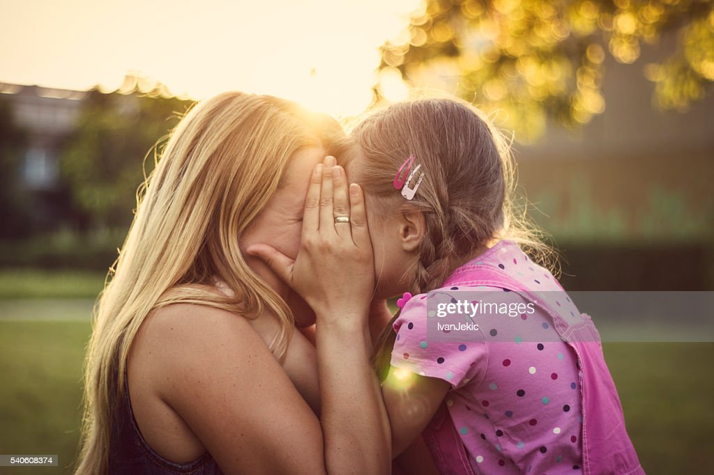 Mother and daughter hiding behind the hand : Stock Photo