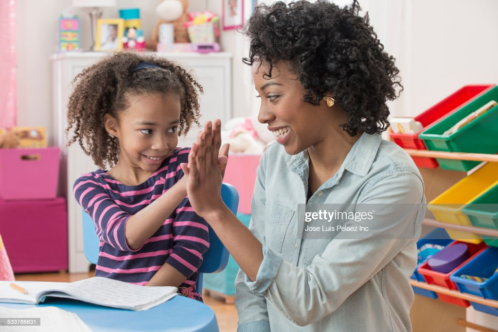 Mother and daughter high-fiving during homework in playroom : Foto stock