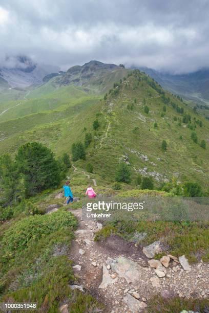 Mutter und Tochter in den österreichischen Alpen Wandern
