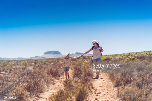 mother and daughter hiking in the mountains reaching out to hands - wilderness area stock pictures, royalty-free photos & images