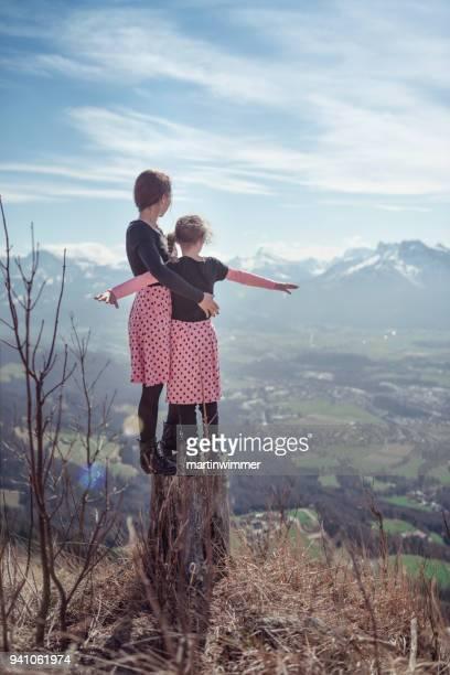 Mutter und Tochter mit rosa Kleid um Berge wandern