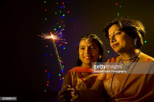 Mother and daughter holding a sparkler on Diwali