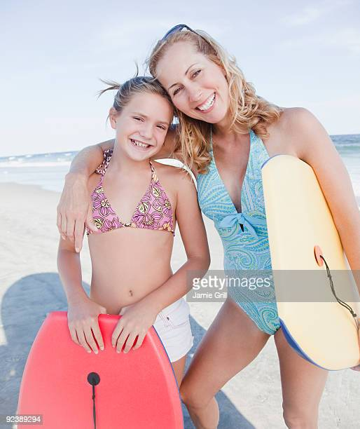 Mother and daughter holding body boards at beach