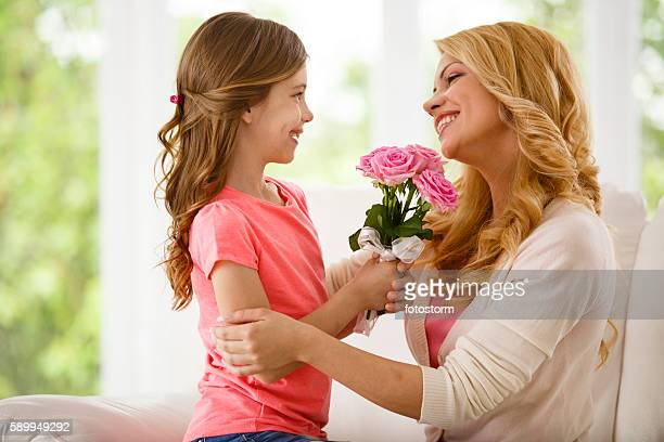 Mother and daughter holding bouquet of flowers