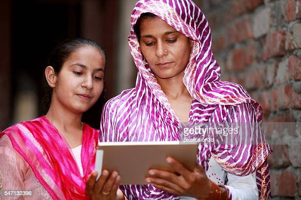 Mother And Daughter Holding Digital Tablet