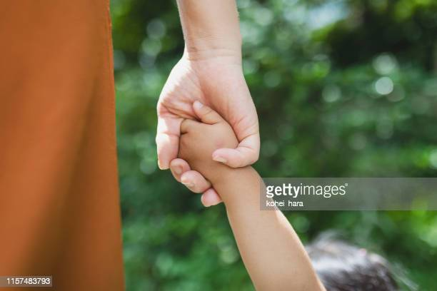 mother and daughter holding each other's hands in the park - childhood stock pictures, royalty-free photos & images