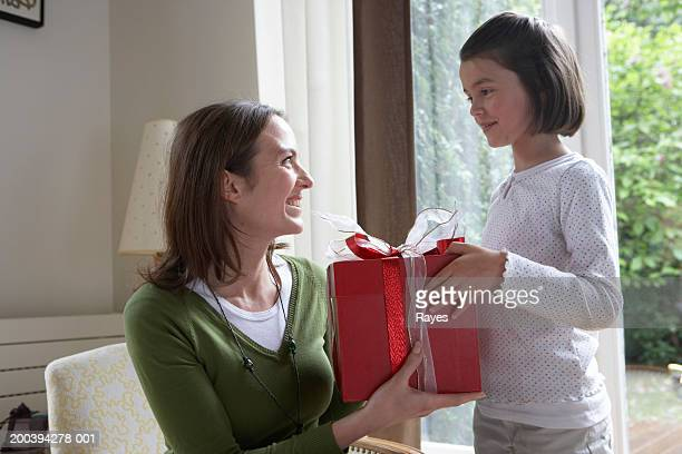 Mother and daughter (6-8) holding gift box, smiling