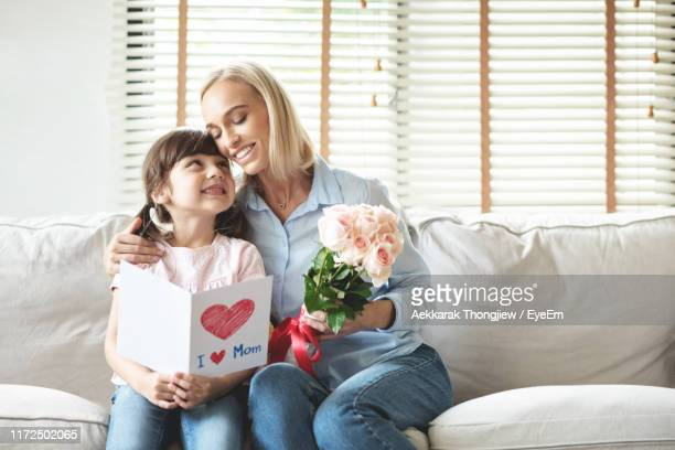 mother and daughter holding gifts while sitting on sofa at home - mothers day card ストックフォトと画像