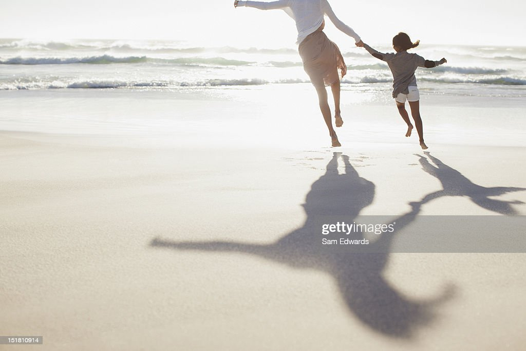 Mother and daughter holding hands and running on sunny beach : Foto de stock